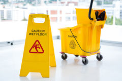 Sigh board with mop bucket in room. Against glass Royalty Free Stock Images
