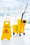 Sigh board and mop bucket in room. Sigh board with mop bucket in room against glass Royalty Free Stock Photo