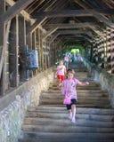 SIGHISOARA, РУМЫНИЯ - 1-ОЕ ИЮЛЯ 2016: Девушки бежать на лестницах ученых, построенных в 1642 в Sighisoara, Румыния Стоковая Фотография RF