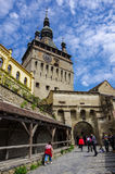 Sighisoara, Romania May 2, 2014: Clock tower sided by old buildi Royalty Free Stock Photos