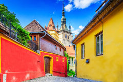 Sighisoara, Romania. Medieval street with Clock Tower in Transylvania Stock Photo