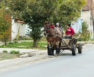 Two young guys ride a horse-drawn cart in a suburb of Sighisoara in Romania. Sighisoara, Romania, October 08, 2017 : Two young guys ride a horse-drawn cart in a Stock Photo