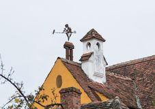 Weathervane in the form of a boy with a pipe and a bird on the roof of a dwelling house in the old city of Sighisoara in Romania. Sighisoara, Romania, October 08 stock photography