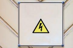 Sighn di rischio elettrico su fondo giallo-chiaro di legno Immagini Stock
