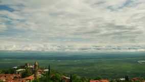 Sighnaghi, Georgia. A view from above of the landscape of the City. Time lapse. The clouds float above the mountains stock footage