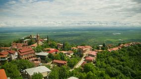Sighnaghi, Georgia. A view from above of the landscape of the city. Time lapse. The clouds float above the mountains stock video footage