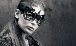 The sight of a beautiful young woman in black lace mask on the eyes. Black and white closeup portrait Stock Photo