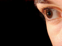 Sight in the future. Closeup of a brown eye with black background royalty free stock photos