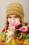 Sight of the girl with tulips. Sight of the girl in yellow cap with tulips Stock Image