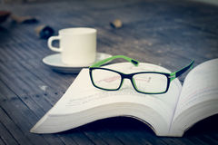 Sight glasses, coffee cup and dried leafs on bamboo floor in vintage Stock Image