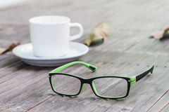 Sight glasses, coffee cup and dried leafs on bamboo floor in vintage Royalty Free Stock Photos