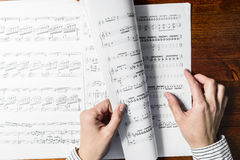 Sight-reading. Female hands sight reading sheet music on wooden background Royalty Free Stock Image