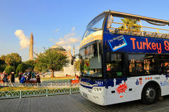 Sight seeing bus and Hagia Sophia. ISTANBUL - JUL 15: Sight seeing tourist bus in front of Hagia Sophia on July 15, 2013 in Istanbul. Sultanahmet Square one of Stock Image