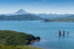 Sights of the Kamchatka Peninsula. View of the gulf of the Pacific Ocean, the cliff `Three Brothers` and the hill Vilyuchinsky volcano in the background Stock Photos