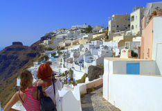 Sightseeing astonishing Santorini island,Greece. Tourists sightseeing astonishing  Santorini island,woman and girl marvel at the beauty and the unique Stock Photos