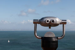 Sightseeing Binoculars Overlooking Ocean with Sailboat in Distance. Stock Image