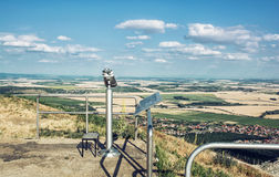 Sightseeing binoculars and slovak landscape with fields and clou Royalty Free Stock Photos