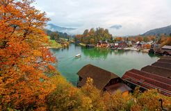 A sightseeing boat cruising on Konigssee  King`s Lake  surrounded by colorful autumn trees and boathouses on a foggy morning. ! Beautiful scenery of Bavarian Stock Photo