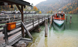 Sightseeing boat parking by a wooden pier at beautiful lakeside in a misty foggy morning on Lake Konigssee Royalty Free Stock Images
