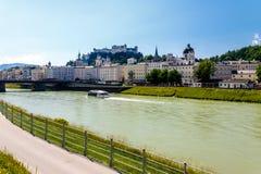 Salzburg, Austria waterfront. Sightseeing boat on river through Salzburg, Austria with waterfront promenade royalty free stock photography