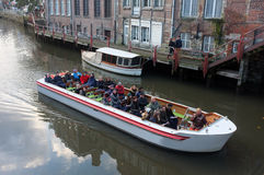 Sightseeing boat tour on a canal. Tourists view the city on a sightseeing boat in Ghent, Belgium Stock Photos