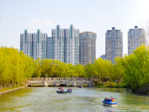 Sightseeing boats. Tourists taking boats traveling Century park with modern apartments buildings background Shanghai China Royalty Free Stock Photos