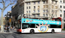Sightseeing Bus in Barcelona, Spain. A city sightseeing bus (Bus Turistic) with tourists is driving on the route in the center of Barcelona, Spain Royalty Free Stock Images