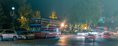 Sightseeing bus on Tbilisi night road. Red sightseeing bus on Tbilisi night road with cars Royalty Free Stock Image