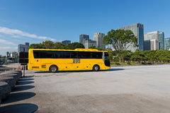 Sightseeing city tours by bus. Big cities and downtowns have the sightseeing tours by tourist buses. A yellow tourist bus stands by a park amidst long skyscraper Stock Photos