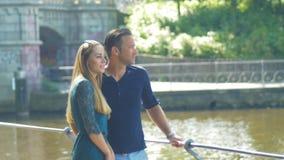 Sightseeing Een paar in liefde die een nieuwe stad bezoeken en rond op de rivieroever kijken stock video