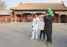 A sightseeing family. A husband holding child on shoulder is sightseeing with his family and taking picture happily at famous Forbbiden City in Beijing, China Stock Photo
