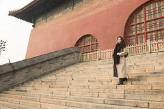 A SIGHTSEEING GIRL. A GIRL IS SIGHTSEEING STANDING ON THE STONE STAIR OF GULOU GATE BUIDLING HAPPILY IN BEIJING, CHINA Stock Images