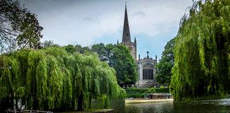 Sightseeing on the river. The river Avon with Holy Trinity church and a sightseeing boat tour Stock Photo