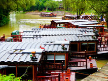 Sightseeing sculling boats lines up. Fishermen rowing oar propelled boats on a river and few stopped at the shore inside Xixi Wetland Park Hangzhou city zhejiang Royalty Free Stock Photos
