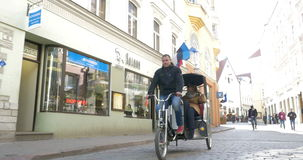 Sightseeing in Tallinn with Cycle Rickshaw. TALLINN, ESTONIA - APRIL 27, 2015: Steadicam shot of two tourists having sightseeing tour in Tallinn in cycle stock video footage