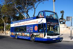 Sightseeing tour bus, Malta. Passengers aboard a bus open topped tour bus with the Independence Monument to the rear, Floriana, Malta, Europe Stock Images
