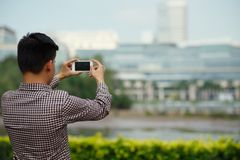 Sightseeing. Tourist taking pictures while going sightseeing, rear view Royalty Free Stock Image
