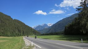 Sightseeing and travel through the Austrian Alps in Europe. Motorcyclist and car on the road between the mountains in the summer Stock Photography