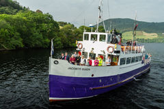 Sightseeing trip in Loch Ness. Loch Ness, Urquhart Castle, Scotland, UK  - September 19, 2014: a Jacobite Cruises boat on approach to Urquhart Castle dock. Their Royalty Free Stock Photos