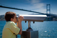 Sightseeing through viewpoint binoculars. Young boy looking through a coin operated viewpoint binoculars at seaside landscape of Istanbul next to a bosphorus Royalty Free Stock Photo