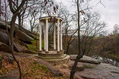 Sightseeing white rotunda or round gazebo on granite rocks and stones on background of the rainy sad autumn landscape. Photo to tr. Ansfer melancholic mood or stock photo
