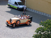 Sightseers make trip at old town by vintage open car Stock Image