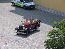 Sightseers make trip at old town by vintage open car Stock Photos