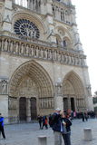 Sightseers outside front entrances to Notre Dame Cathedral,Paris,France,2016. Gorgeous architecture of the Notre Dame Cathedral, with several sightseers standing Stock Images