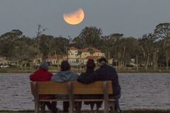 Sightseers watch supermoon eclipse. A group of sightseers sit on a bench by the Halifax River in Ormond Beach, FL and watches the setting supermoon as a lunar Stock Photo