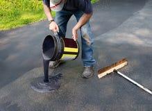 Sigillante di versamento dell'asfalto sulla strada privata fotografie stock libere da diritti