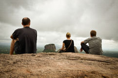 Three people sitting on Sigirya rock Stock Photos