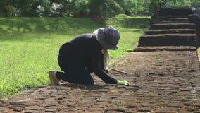 SIGIRIYA, SRI LANKA - FEBRUAR 2014: Die Ansicht des weiblichen Gärtners arbeitend in Sigiriya arbeitet, ein alter Palast im Garte stock footage