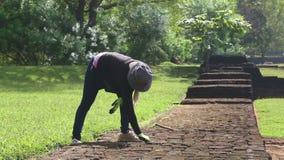SIGIRIYA, SRI LANKA - FEBRUAR 2014: Die Ansicht des weiblichen Gärtners arbeitend in Sigiriya arbeitet, ein alter Palast im Garte stock video