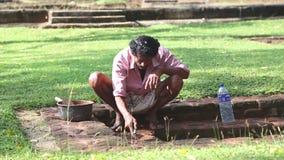 SIGIRIYA, SRI LANKA - FEBRUAR 2014: Mann, der Erhaltungsarbeit in Sigiriya, ein alter Palast gelegen im zentralen Matale Dist erl stock video footage
